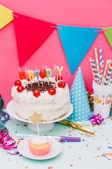 Cupcake in front of cake on cake stand with party decoration