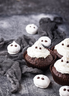 幽霊の形をしたカップケーキ。子供のパーティーのためのハロウィーンのおやつ