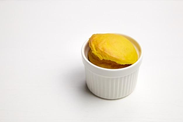 コピースペースを持つ白い木製の背景に白いセラミックラメキンベーキングボウルのカップケーキ。セラミックカップの単一のマフィン、セレクティブフォーカス