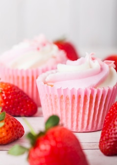 Cupcake muffin with strawberry cream dessert on wooden table with fresh strawberries