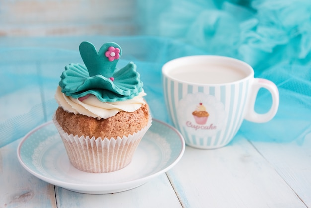 Cupcake and a mug on turquoise background. bright blue wooden table