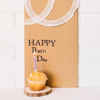 挨拶のあるボール紙の近くのカップケーキ