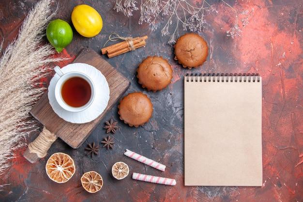 カップケーキノートブック柑橘系の果物シナモンボード上のお茶のカップ