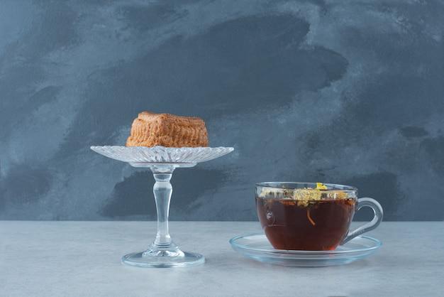 暗い背景に熱いハーブティーとガラスプレート上のカップケーキ。高品質の写真