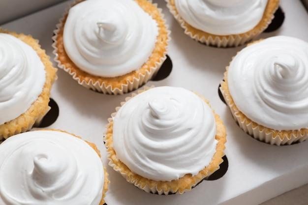 Упаковка кексов, коробка доставки, ванильные кексы с белым кремом, выборочный фокус, крупный план