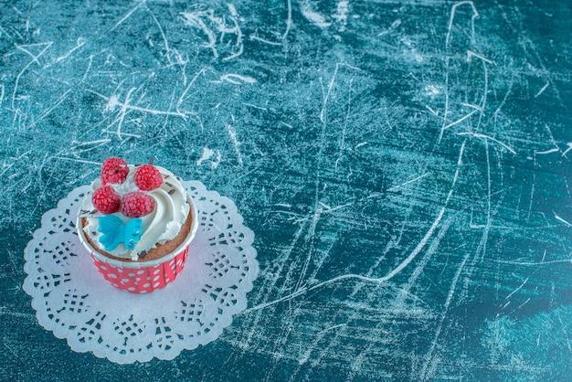 Cupcake in un caso di tortino su un centrino, su sfondo blu. foto di alta qualità