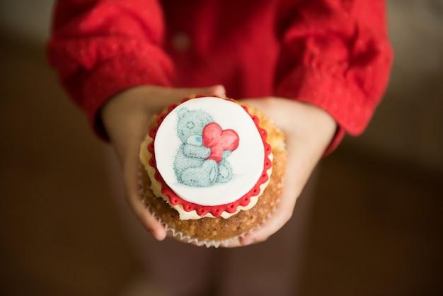 Кекс тедди с сердцем в руке. праздник валентина. выборочный фокус.