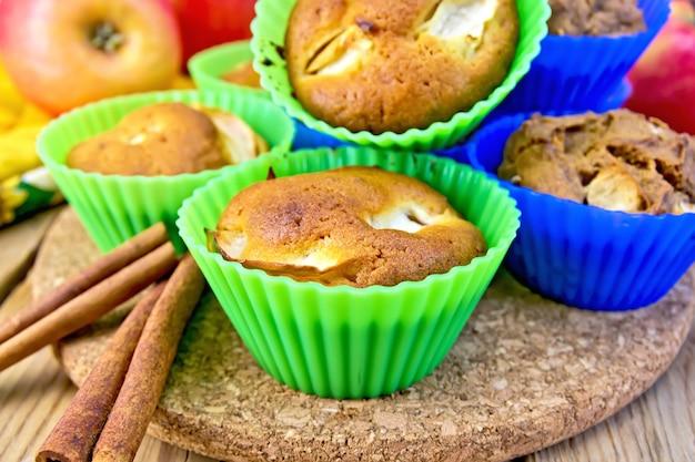 실리콘 몰드에 사과를 넣은 컵케이크 밀과 호밀, 계피, 나무 판자 배경에 냅킨