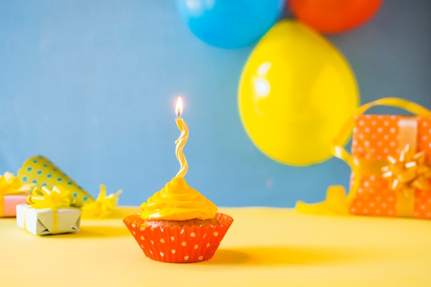 Cupcake with burning candle on yellow surface