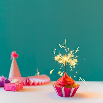 Cupcake with burning sparkler against green background