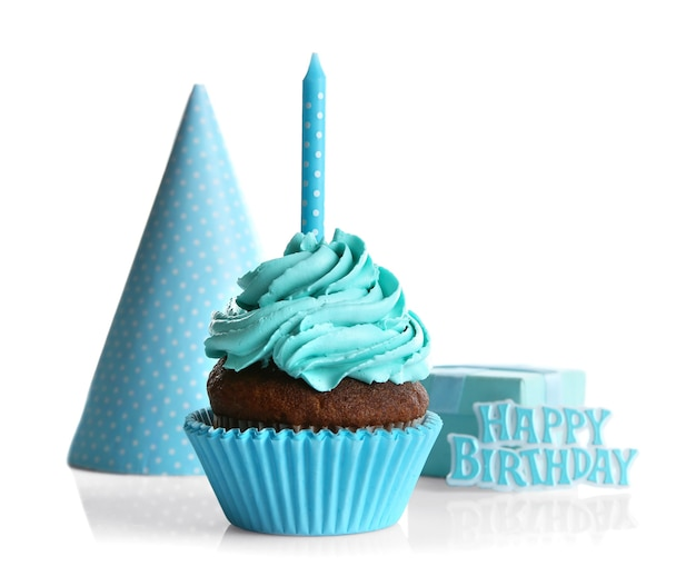 Cupcake with candle and party hat on white background
