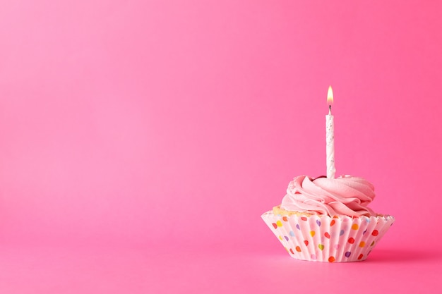 Cupcake with candle on pink background, space for text