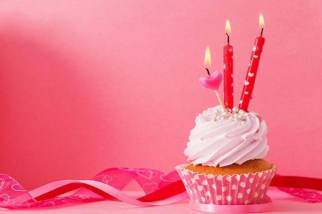 Cupcake with candle on pink background
