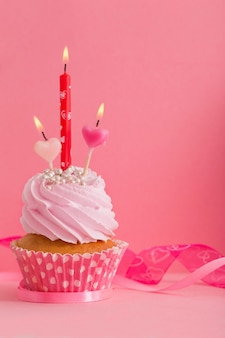 Cupcake with candle on pink