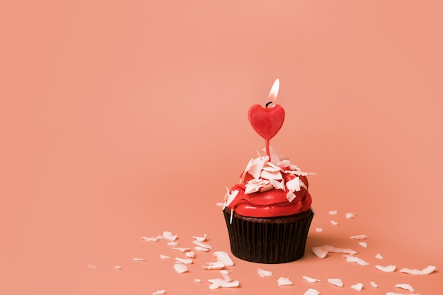 Cupcake with candle in the shape of a heart - sweets for valentine's day with copy space