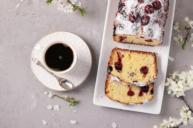 灰色のコンクリートの背景とコーヒーの白いプレートにあるチェリーとカップケーキ、水平形式、クローズアップ、上面図