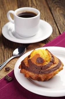 木製のテーブルにチョコレートとコーヒーのカップケーキ