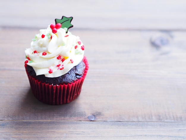 Cupcake with christmas tree shape on wooden table.