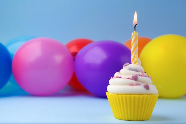 Кекс с разноцветной свечой на день рождения и воздушными шарами