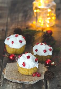 クリームとザクロの装飾が施されたカップケーキ