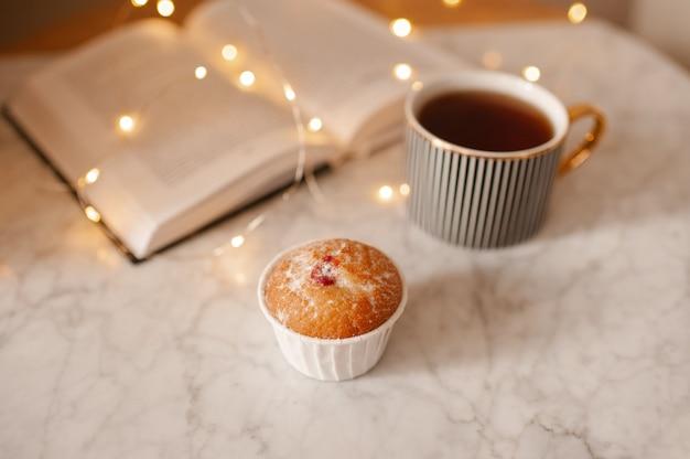 大理石のコーヒーテーブルにお茶と紙の本とカップケーキ
