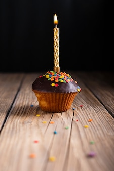 Cupcake with glaze and lit candle