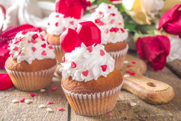 Cupcake with heart for valentines. valentine day sweet dessert, vanilla cupcakes with whipped vanilla cream and red sugar hearts decor for valentine's day, wooden table with rose flowers bouquet