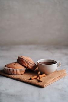 ホットチョコレートと数枚のシナモンが入った茶色の繊維布に粉砂糖ガラスをかけたカップケーキ。スペースをコピーします。