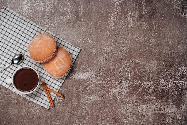 ホットチョコレートとシナモンのいくつかの部分と木の板に粉砂糖とカップケーキ。上面図。スペースをコピーします。