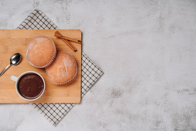 Cupcake with icing sugar on a wooden board with hot chocolate and a few pieces of cinnamon. top view. copy space.