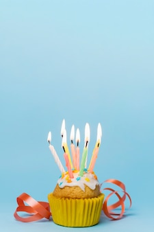 Cupcake with lit candles and ribbon