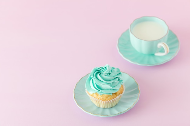 Cupcake with mint cream decoration and cup of milk on pink pastel background with copy space