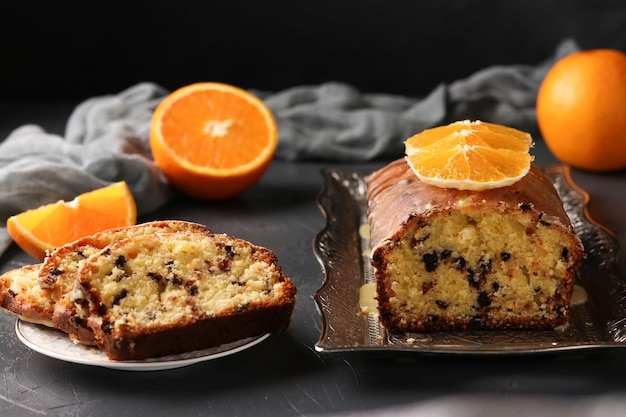 Cupcake with oranges and chocolate located on a tray against a dark background