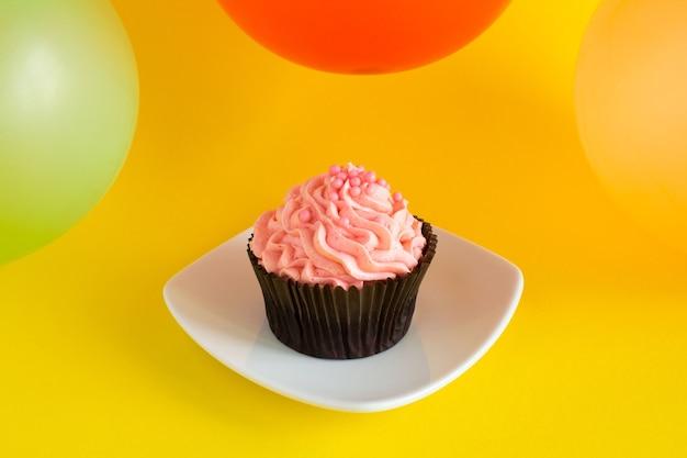 Кекс с розовым кремом и разноцветными шарами на желтом фоне