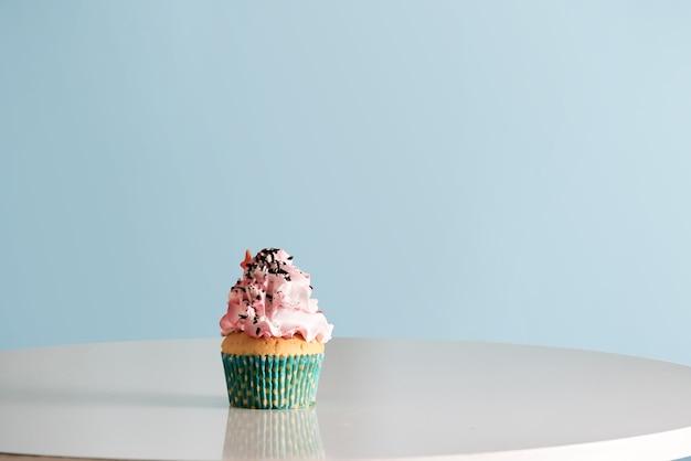 テーブルの上のピンクのクリームのアイシングとカップケーキ