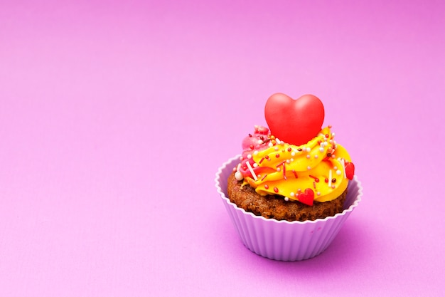 Cupcake with a red heart on a pink background. . happy valentines day concept