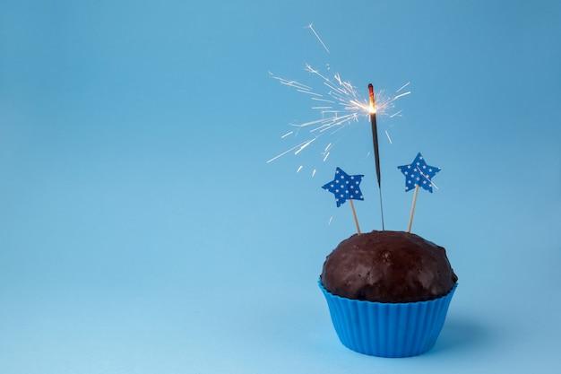 青い背景に線香花火でカップケーキ