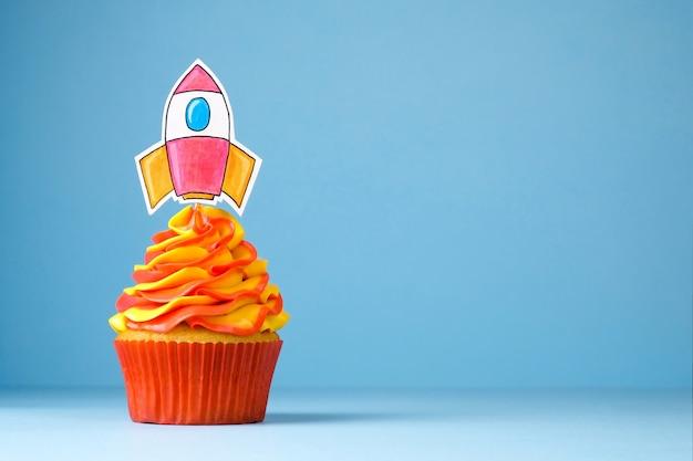 Кекс с запуском ракеты, украшенный взбитыми сливками