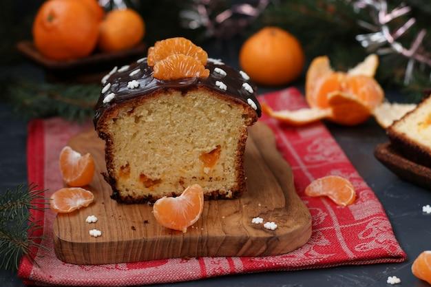 Кекс с мандаринами, покрытый шоколадной глазурью, расположен на новогоднем фоне, праздничный натюрморт.