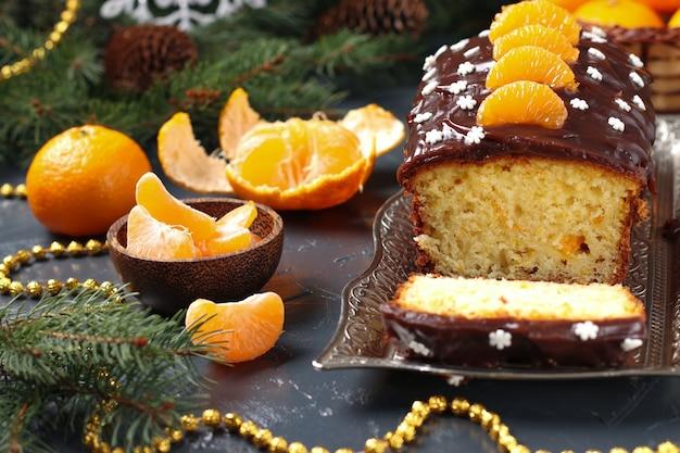 Кекс с мандаринами, покрытый шоколадной глазурью, расположен на новогоднем фоне.