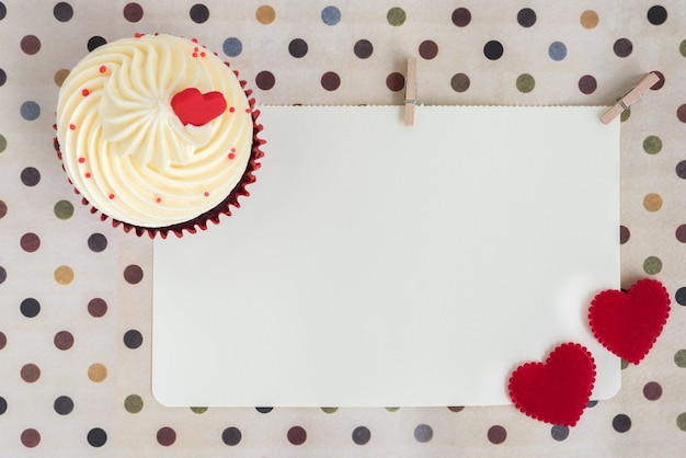 Cupcake with two red hearts over blank paper