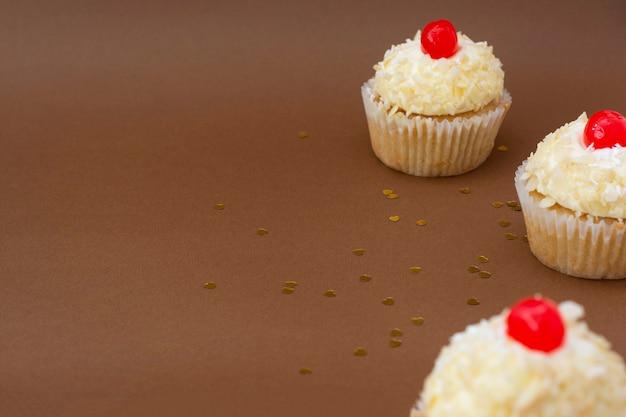 Кекс с ванильным сливочным кремом, коричневый фон, концепция дня рождения. сладкий десерт.