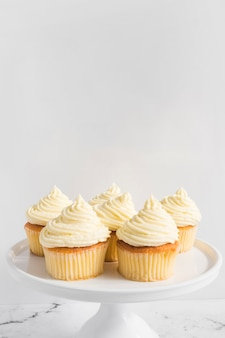 Cupcake with whipped cream on cake stand against white backdrop