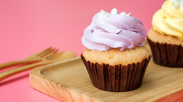 Cupcake on a wooden plate and pink background.