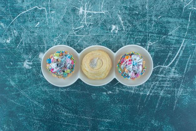 컵 케이크와 파란색 배경에 작은 봉사 플래터에 쿠키. 고품질 사진