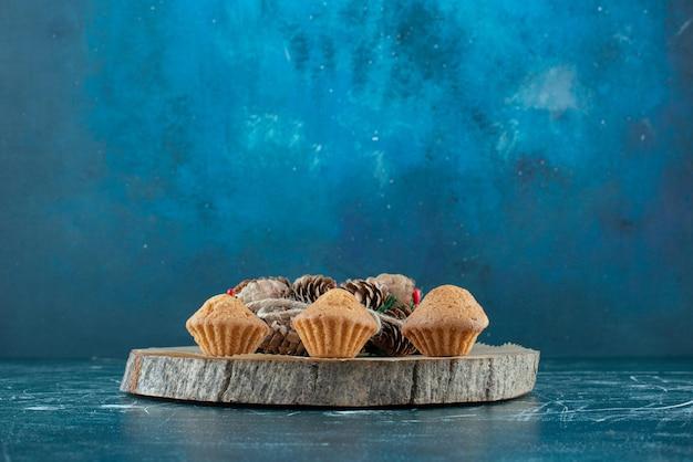 컵케이크와 소나무 화환은 파란색 나무 판자에 배열되어 있습니다.