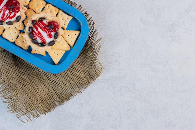 大理石のテーブルの上の青い大皿のカップケーキとクラッカー。