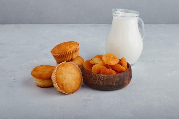 灰色の背景に牛乳の瓶とカップケーキとドライアプリコット。