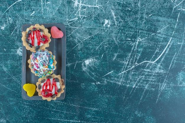 Кексы и мармелады на блюде на синем фоне. фото высокого качества