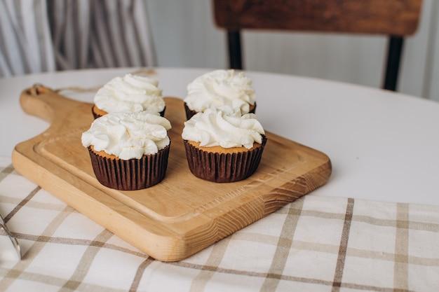 繊細なホイップクリームとカップケーキとマフィンは木の板の上に立っています